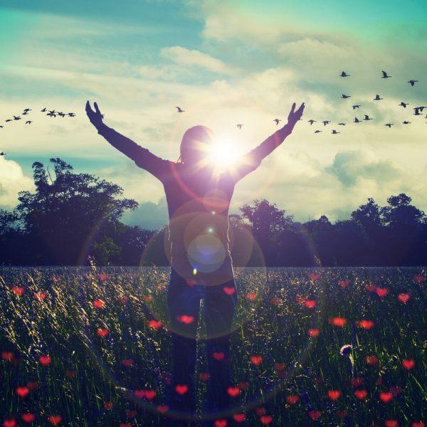 Frau in einer Wiese hebt die Arme und fühlt die Freiheit