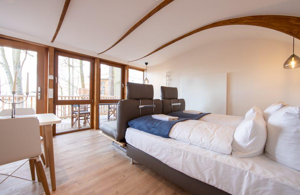 Doppelbett mit Sicht auf große Terrasse