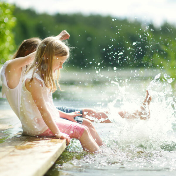 Kinder, die auf einem Steg mit Wasser spielen