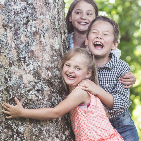 lachende Kinder hinter einem Baum