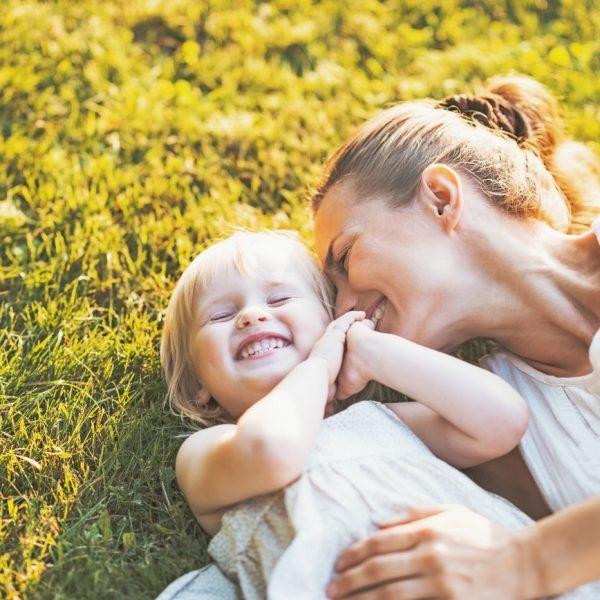 Mutter kuschelt mit ihrer Tochter auf einer Wiese