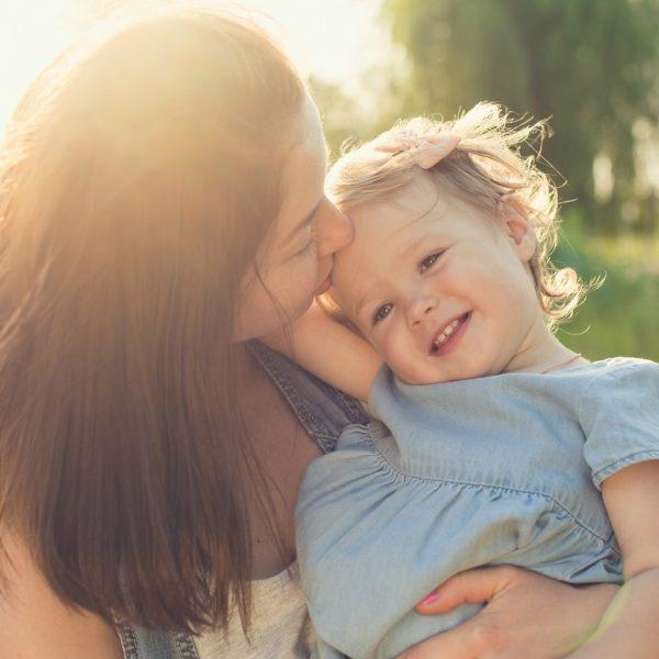 Mutter küsst ihrer Tochter auf die Stirn