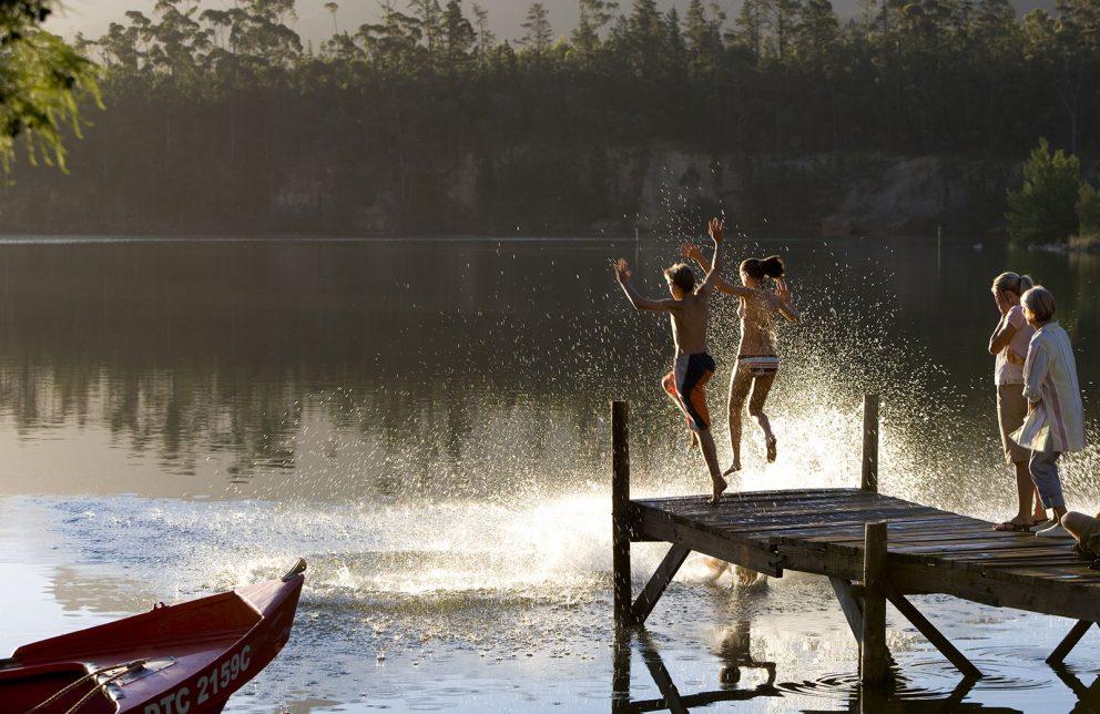 Kinder Springen in den See bei Sonnenuntergang