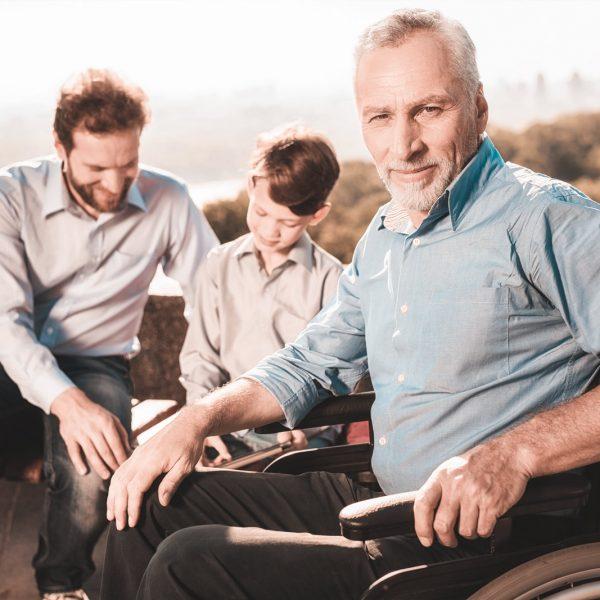Mann im Rollstuhl mit Seinem Sohn und seinem Enkel im Hintergrund