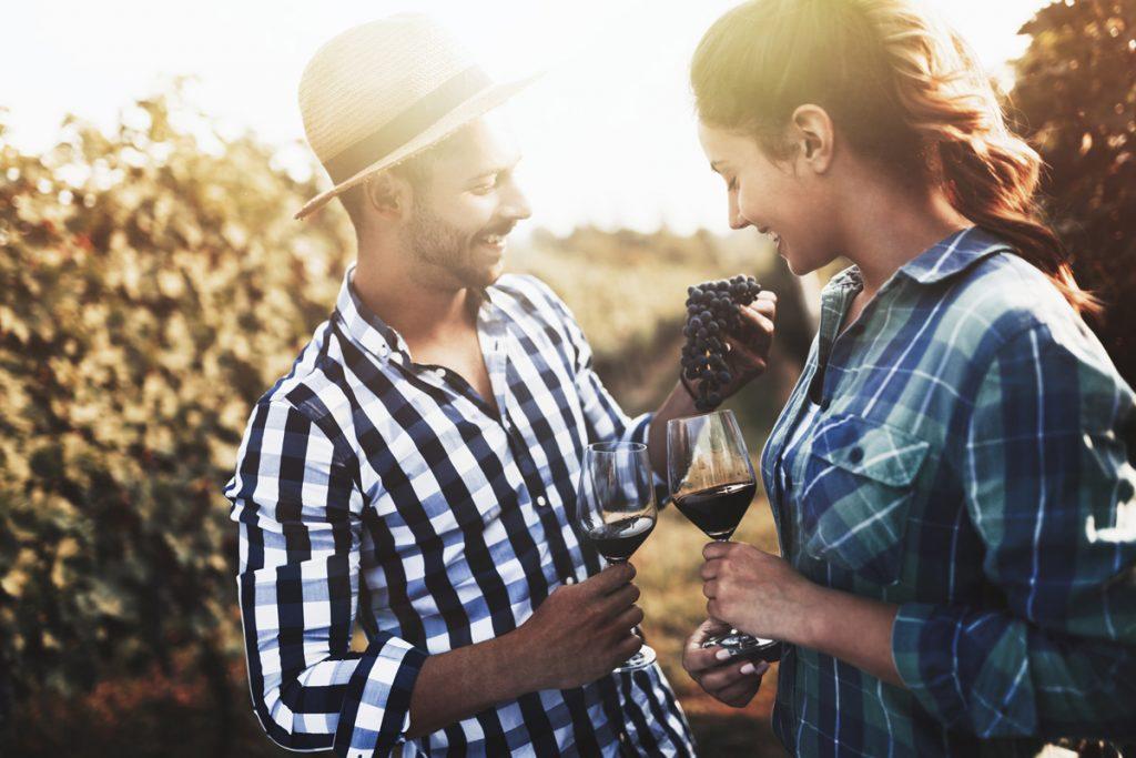 paar trinkt Wein im Traubenfeld