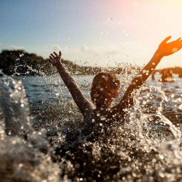 Kind planscht im See bei Sonnenuntergang