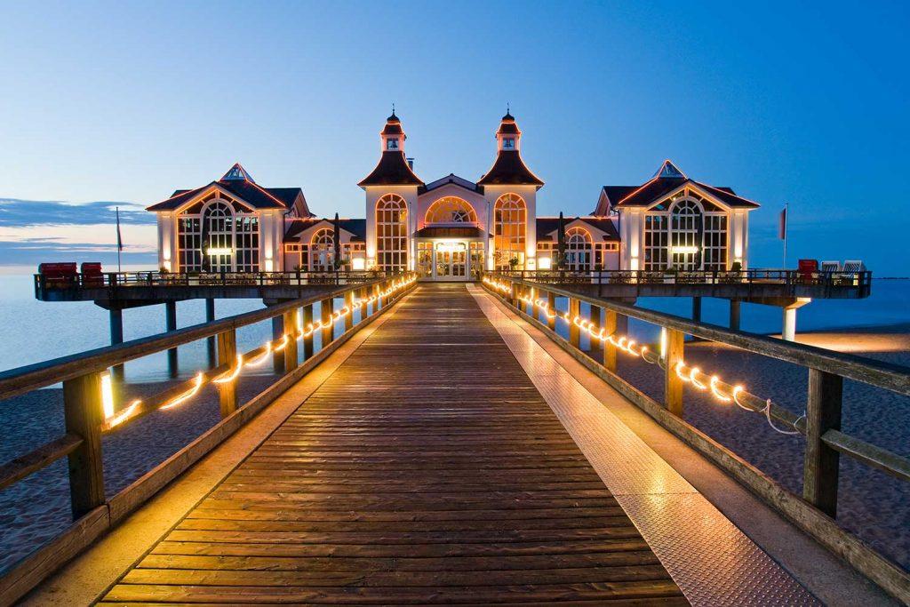 beleuchtete Brücke zu einem schönen Gebäude über dem Strand