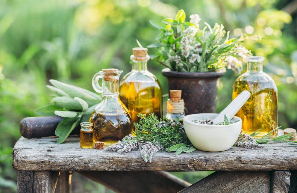 Kräuter und Öl auf einem Tisch in der Natur