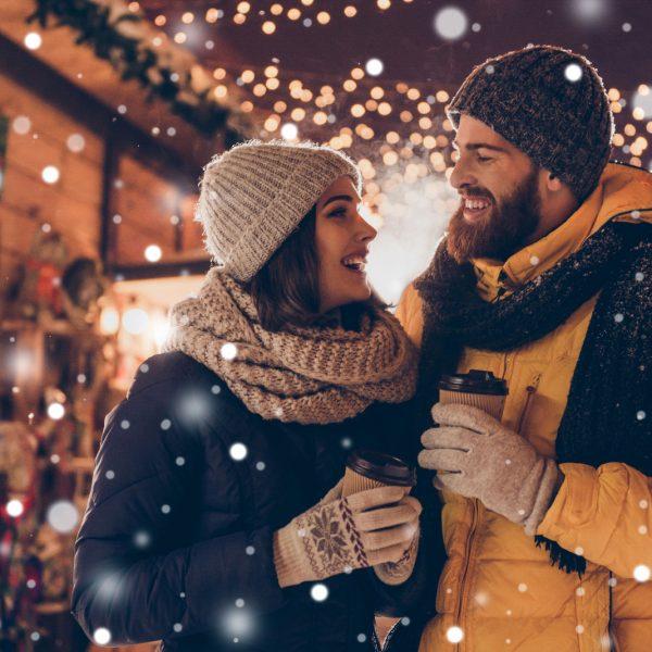 Paar auf dem Weihnachtsmarkt genießt Glühwein