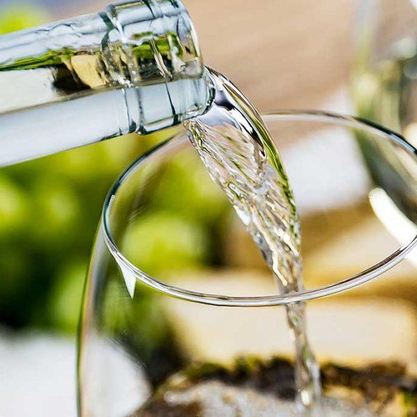 leckerer Weißwein wird in ein Weinglas gefüllt
