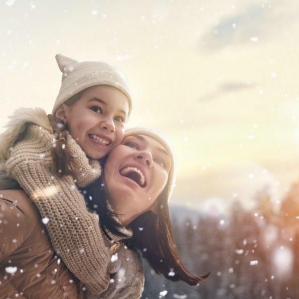 Mutter und Tochter lachen während es schneit
