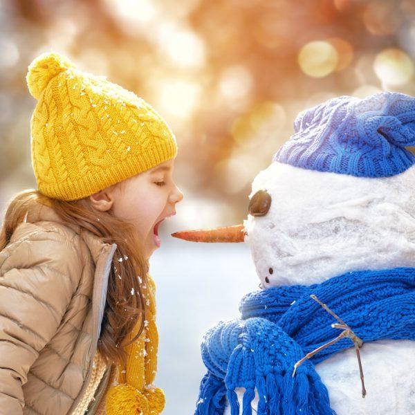 Mädchen will die Nase eines Schneemanns essen