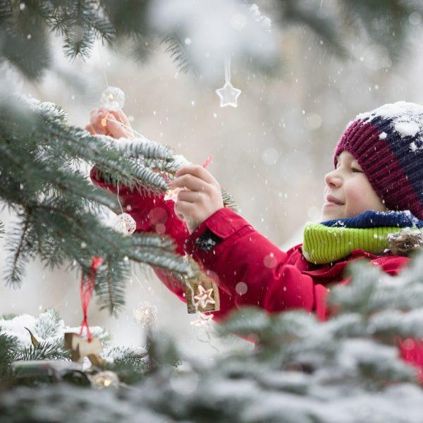 kind schmückt den Tannenbaum für Weihnachten