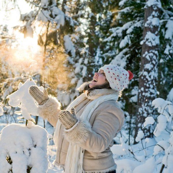 Frau freut sich über den Schnee im Wald